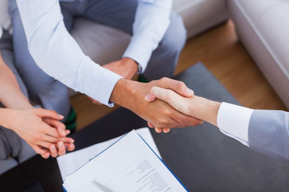 Executive shaking hands with client after signing contract