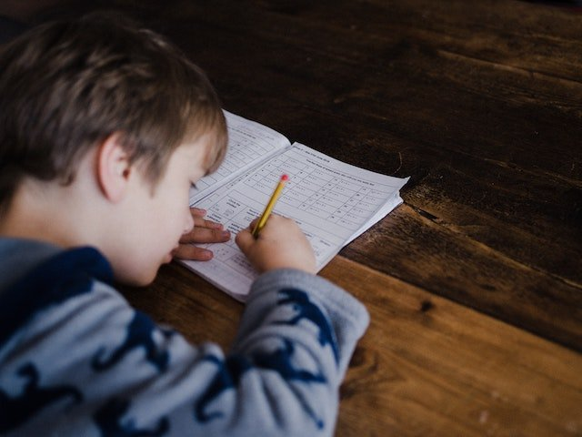 A young boy taking a test with a pencil and paper